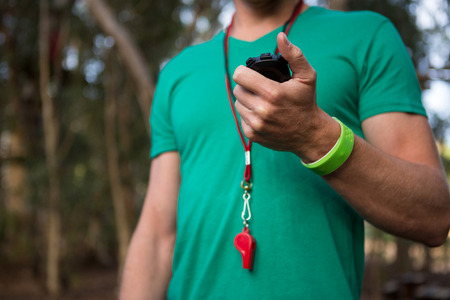 Close-up of trainer holding stop watch in his hand in the forest Foto de archivo