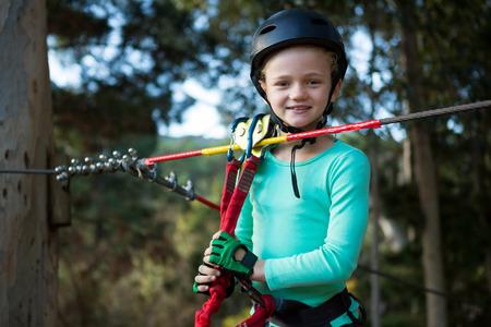 Little girl wearing helmet standing near zip line in the forest Stock Photo