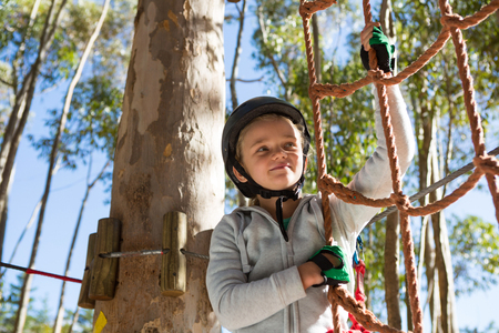 Little girl wearing helmet getting ready to climb on rope fence in the forest
