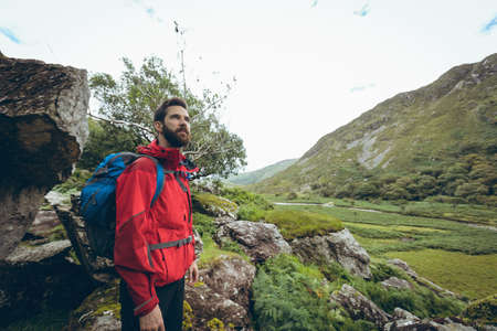 Male hiker standing with backpack in countryside