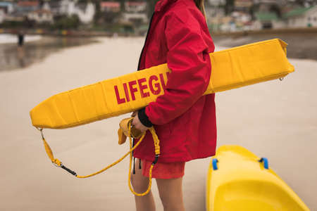 Close-up of female lifeguard holding float in her arm
