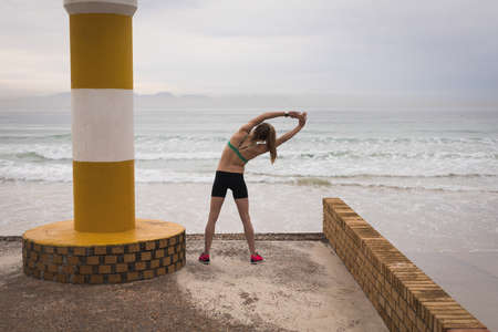 Woman performing stretching exercise near lighthouse at beach
