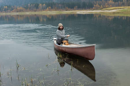 Man oaring canoe in river with his dog LANG_EVOIMAGES