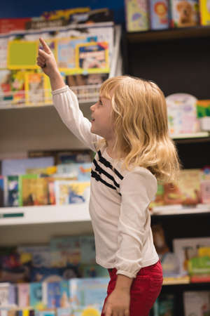 Girl pointing at distant in book store