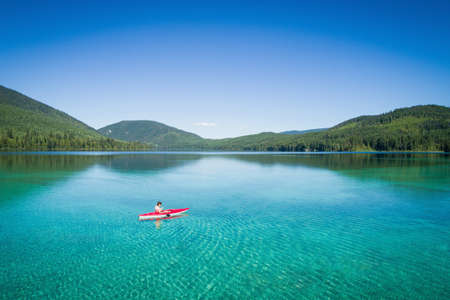Kayaker kayaking in shallow turquoise water on a sunny day
