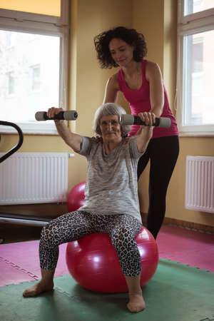 Female therapist assisting senior woman with dumbbells in nursing home