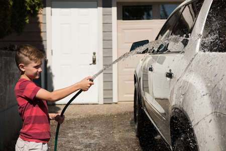 Boy washing a car at outside garage on a sunny day