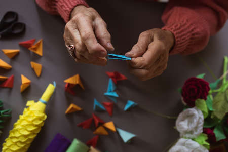 Senior woman doing craft work at nursing home LANG_EVOIMAGES