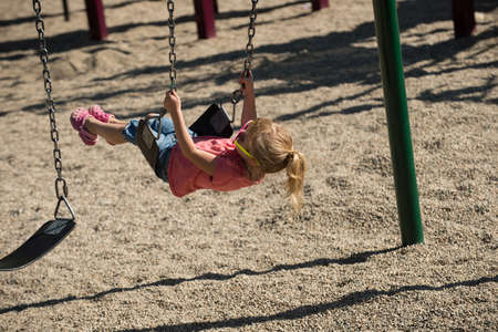 Cute girl playing on swing in park