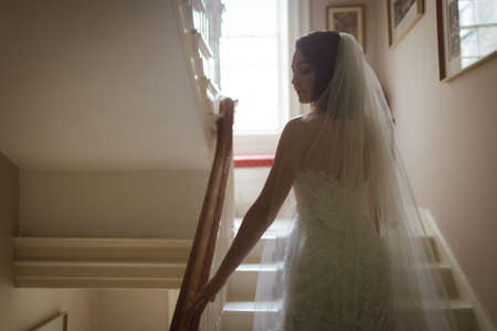 Bride looking sideways while climbing the steps at home