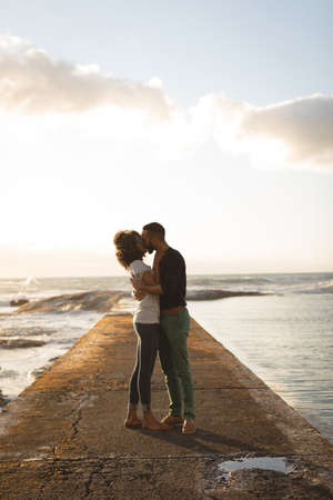 Romantic couple kissing while standing on a jetty during sunset