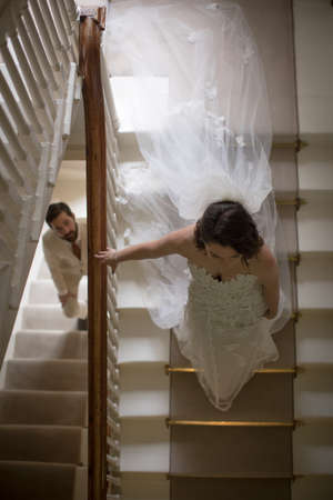 Bride and groom walking on the staircase at home