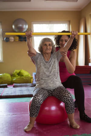 Female therapist assisting senior woman with exercise stick and exercise ball in nursing home
