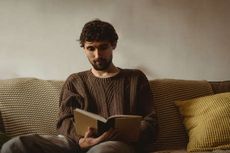 Man reading book in living room at home