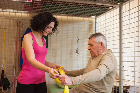 Female therapist assisting senior man with exercise band in nursing home