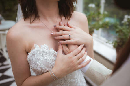Close-up of groom placing his hand on brides chest