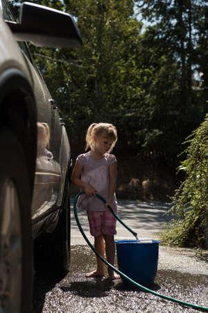 Girl filling water in bucket while washing car