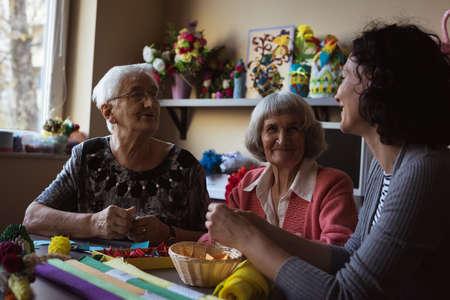 Two senior women interacting with caretaker at nursing home LANG_EVOIMAGES
