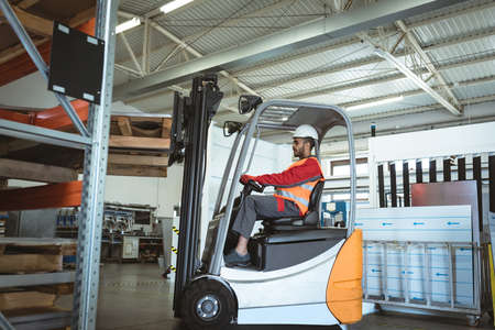 Male worker driving forklift in the warehouse