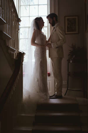 Bride and groom holding hands on the steps at home LANG_EVOIMAGES