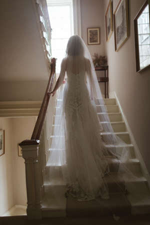 Rear view of bride climbing up the staircase at home