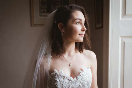 Smiling bride looking out of the window at home
