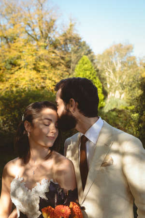 Groom kissing on brides forehead in the garden