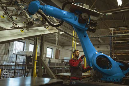 Male worker checking robotic machine in the factory