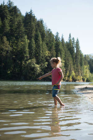 Girl playing in river on a sunny day
