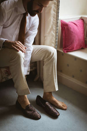Groom wearing his shoes at home