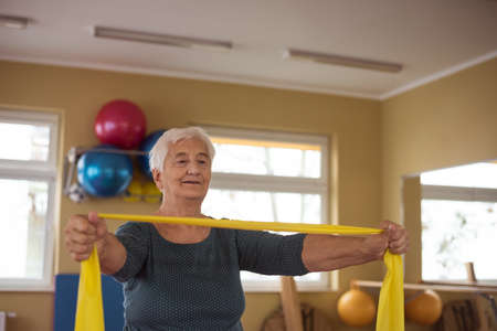 Senior woman performing exercise with exercise band LANG_EVOIMAGES