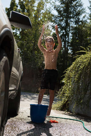 Boy playing with water while washing car at outside garage