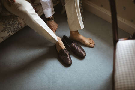 Close-up of groom wearing his shoes at home LANG_EVOIMAGES