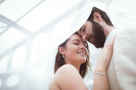 Close-up of smiling bride and groom standing under the veil