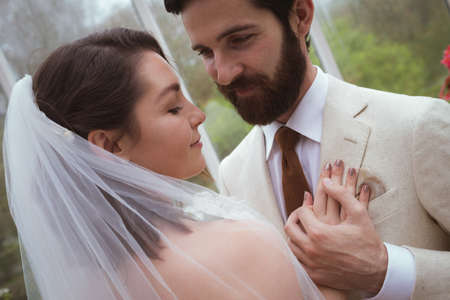 Close-up of romantic bride and groom embracing