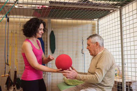 Female therapist assisting senior man with exercise ball in nursing home