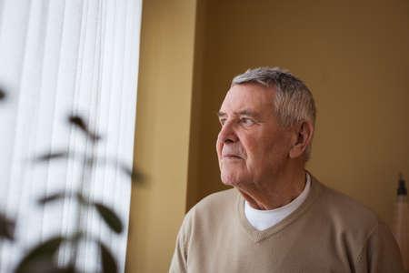 Thoughtful senior man standing at nursing home