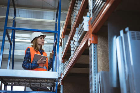 Female worker maintaining record on digital tablet at factory warehouse