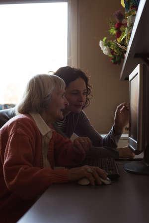 Caretaker assisting senior woman while working on computer at nursing room LANG_EVOIMAGES