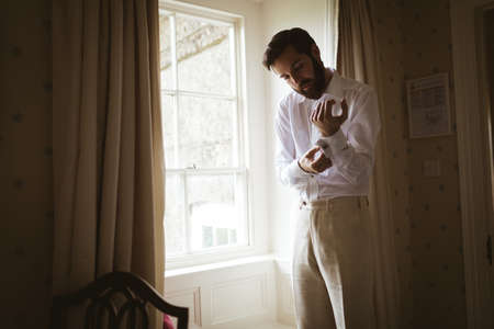 Groom getting dressed at home near the window