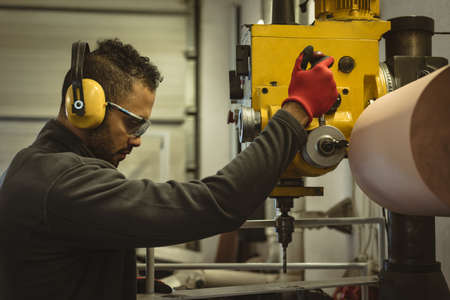 Male worker operating a machine in the factory LANG_EVOIMAGES