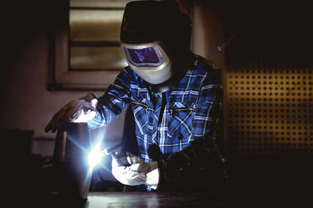 Worker working on manufactured metal parts in the factory