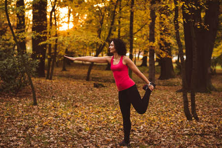 Woman performing stretching exercise in forest on a sunny day