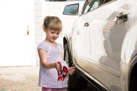 Girl washing a car at outside garage on a sunny day