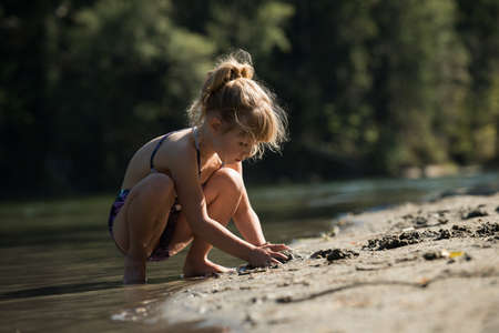 Girl playing with sand near riverbank on a sunny day
