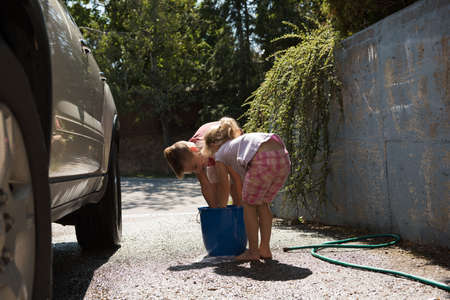 Siblings washing a car at outside garage on a sunny day LANG_EVOIMAGES