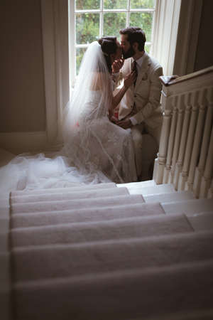 Romantic bride and groom sitting on the window sill and kissing