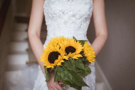 Mid section of bride holding a flower bouquet