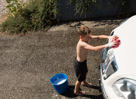Boy washing a car at outside garage on a sunny day
