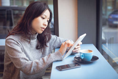 Beautiful woman using digital tablet while having coffee in cafeteria LANG_EVOIMAGES